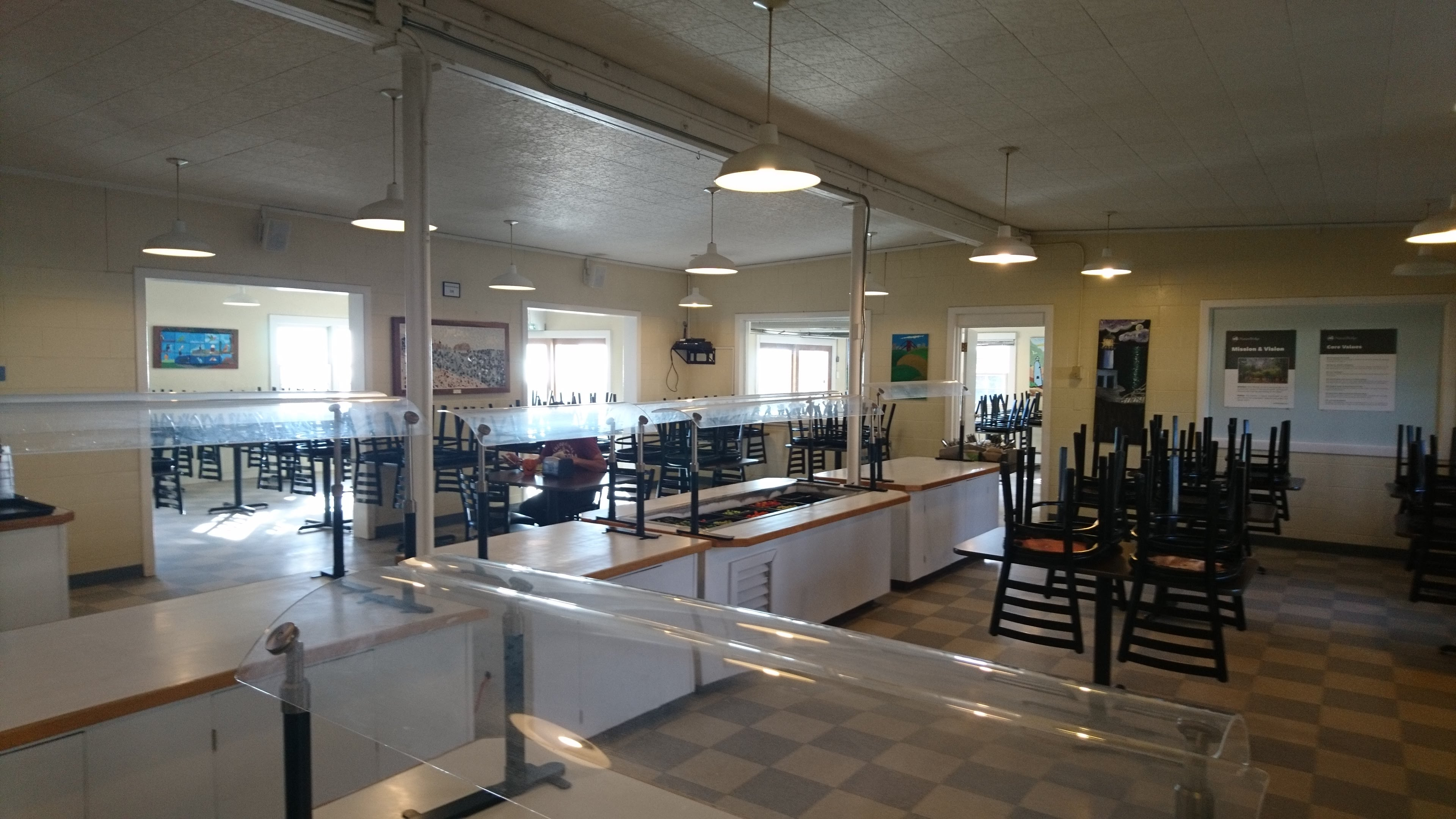 Photo of inside of dining hall. Buffet and several tables.